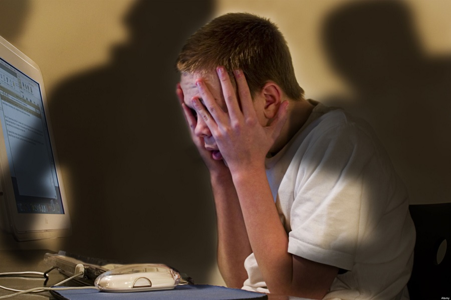 Cyber bullying concept - shadowy figures menace boy at computer. Image shot 2009. Exact date unknown.